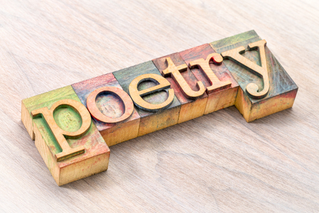 poetry word abstract- text in vintage  letterpress wood type blocks against grained wood