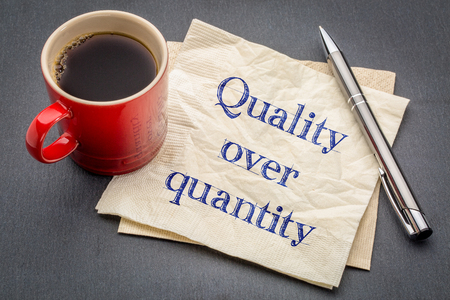 quality over quantity inspirational reminder note - handwriting on a napkin with cup of coffee against gray slate stone background Stock Photo