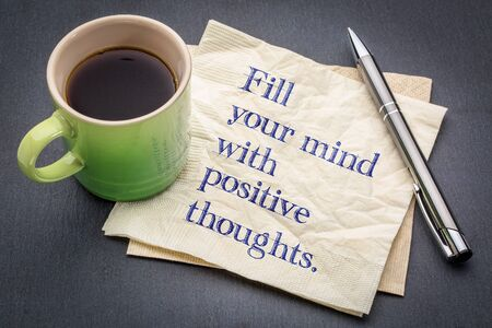 Fill your mind with positive thoughts - inspirational handwriting on a napkin with cup of coffee against gray slate stone background