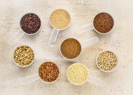 gluten free grains (quinoa, brown rice, kaniwa, amaranth, sorghum, millet, buckwheat, teff) - a set of measuring scoops on a rustic barn wood Stock Photo