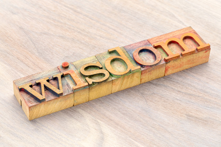 wisdom word abstract in letterprtess wood type blocks stained by color inks Stock Photo