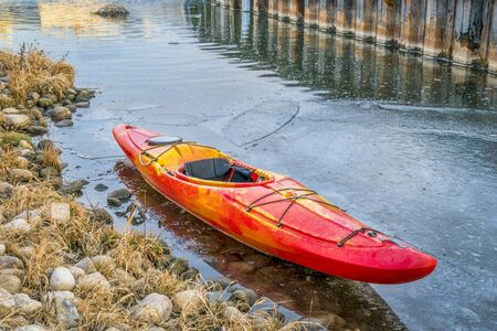 winter kayaking in Colorado - red whitewater kayak with on shore of icy St Vrain Creek Imagens