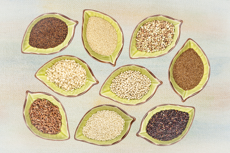 nine gluten free grains (black quinoa, buckwheat, amaranth, teff, sorghum, kaniwa, millet, and brown rice) - top view of leaf shaped ceramic bowls against painted canvas