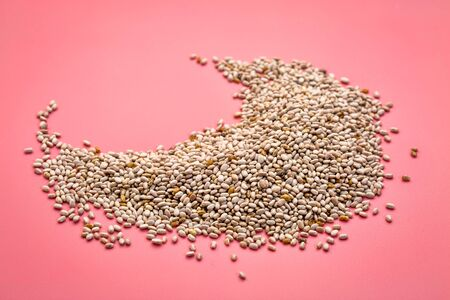 a small pile  of organic white chia seeds rich in omega-3 fatty acids on a pink background Stock Photo
