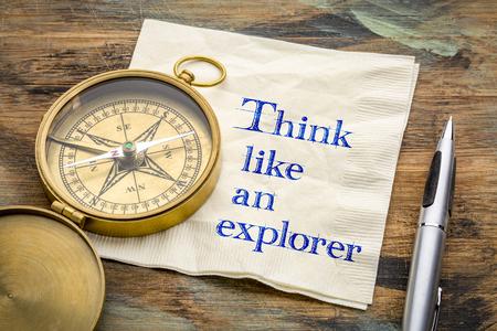 Think like an explorer - inspiraitonal handwriting on a napkin with an antique brass compass