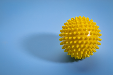 spiky rubber  ball roller for self massage, reflexology and myofascial release, blue background with a shadow