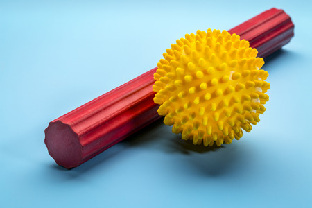 spiky rubber  ball and roller bar for self massage, reflexology and myofascial release, blue background with a shadow Stok Fotoğraf - 95901459