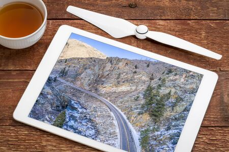Poudre River canyon with a scenic road in winter scenery, reviewing an aerial image on a digital tablet Stock Photo