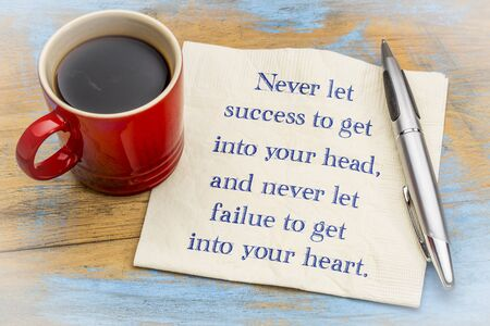 Never let success to get into yout head, never let failure to get into your heart - handwriting on a napkin with a cup of coffee