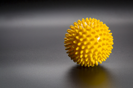 spiky rubber  ball roller for self massage, reflexology and myofascial release, black background with a shadow Stock Photo