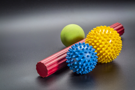 self massage and reflexology therapy concept - a set of small rubber balls and roller bar agianst black background
