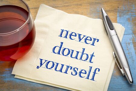 Never doubt yourself  - handwriting on a napkin with a cup of tea Фото со стока
