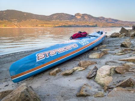 Fort Collins, CO, USA - September 3, 2017: Racing stand up paddleboard (All Star by Starboard) on a calm Horsetooth Reservoir at sunrise during Labor Day weekend. A few minutes later the lake was filled with power boats.