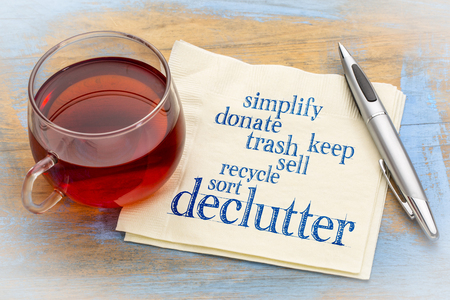 declutter and simplify word cloud on a napkin with a cup of tea Stock Photo