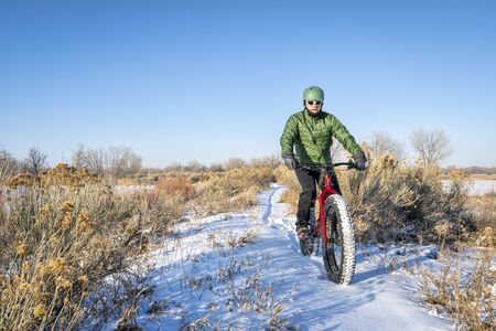 a male cyclist is riding a fat mountain bike in winter, cold day in northern Colorado Stock Photo