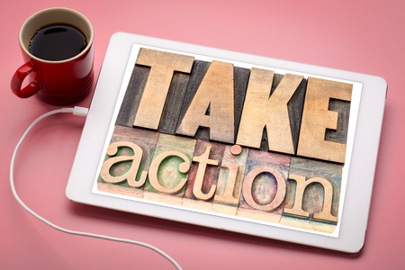 take action - motivation concept -  word abstract in vintage letterpress wood type on a digital tablet with a cup of coffee