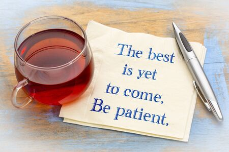 The best is yet to come. Be patient. Inspirational handwriting on a napkin with a cup of tea.
