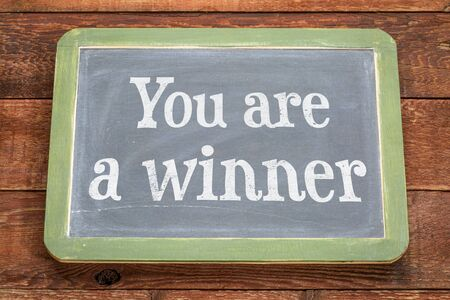 You are a winner.  White chalk text on a vintage slate blackboard against rustic barn wood.
