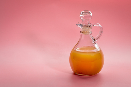 unfiltered, raw apple cider vinegar with mother - a glass cruet against pink background Stock Photo