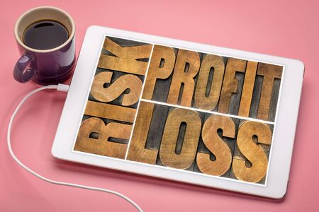 business or investment concept - risk, profit, loss word abstract  in vintage letterpress wood type on a digital tablet with a cup of coffee