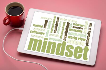 mindset  word cloud on a digital tablet with a cup of coffee
