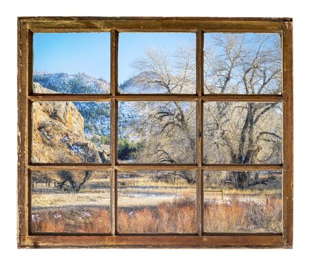 mountain valley with pastures as seen  through vintage, grunge, sash window with dirty glass