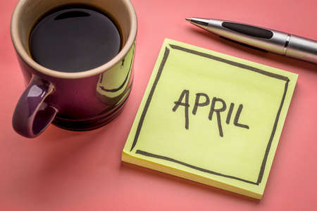 April  - handwriting in black ink on a sticky note with a cup of coffee Stock Photo