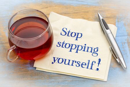 Stop stopping yourself advice - handwriting on napkin with a cup of tea