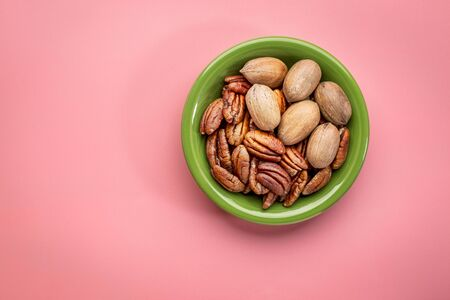 pecan nuts in a ceramic bowl against pink background with a copy space