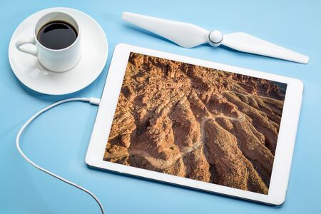 Canyon road - aerial photography concept, reviewing aerial image on a digital tablet with a cup of coffee