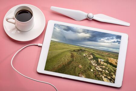 prairie and rock formations - aerial photography concept, reviewing aerial image on a digital tablet with a cup of coffee