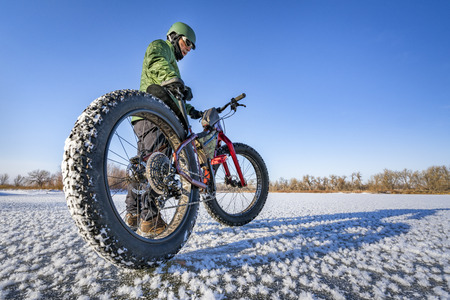 a male cyclist with his fat mountain bike on a frozen lake in northern Colorado, wide angle lens perspective Stock Photo