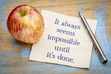 It always seems impossible until it is done - handwriting on a napkin with an apple. Stok Fotoğraf