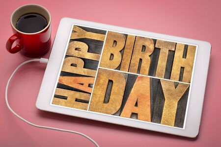 Happy birthday - greeting card in vintage letterpress wood type on a digital tablet with a cup of coffee