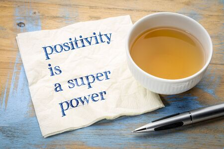 Positivity is a super power - inspiraitonal handwriting on a napkin with a cup of tea Stock Photo