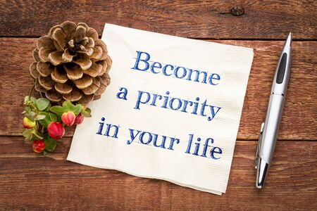Become a priority in your life inspirational handwriting on a napkin on a rustic wooden table