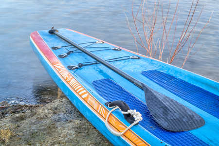 a racing stand up paddleboard with a a paddle on a lake shore