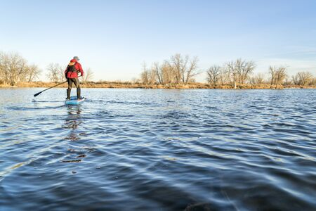 stand up paddling on a lake in Colorado, winter or early spring scenery