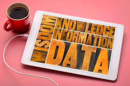 data, information, knowledge and wisdom - text in vintage letterpress wood type on a digital tablet with a cup of coffee Stock Photo