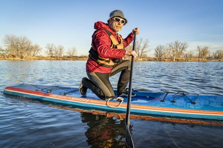 senior male paddler on a racing stand up paddle board, a lake in Colorado in winter or early spring scenery