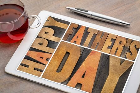 happy fathers day - a word abstract in vintagewood letterpress printing blocks on a digital tablet with a cup of tea