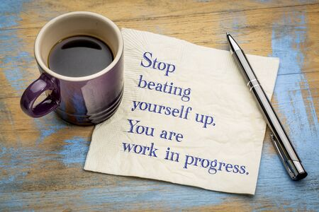 Stop beating yourself up. You are work in progress.  Handwriting on a napkin with a cup of coffee Stock Photo