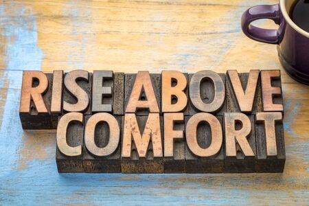 rise above comfort - inspirational word abstract in vintage letterpress printing blocks with a cup of coffee