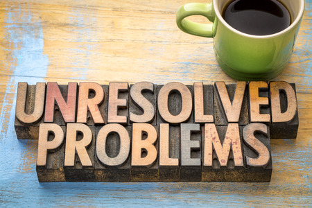 unresolved problems - word abstract in vintage letterpress printing blocks with a cup of coffee Stock Photo