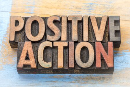 positive action - word abstract in vintage letterpress printing blocks