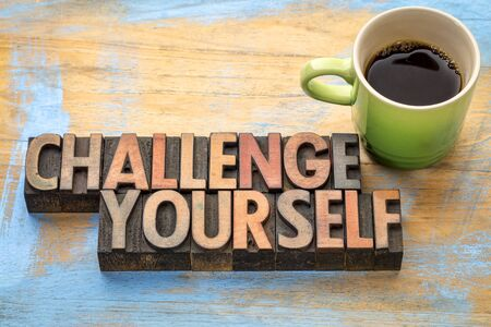 challenge yourself - word abstract in vintage letterpress printing blocks with a cup of coffee
