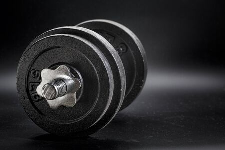 fitness concept - iron dumbbell on a black background, black and white image