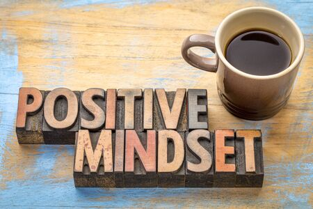 positive mindset - word abstract in vintage letterpress printing blocks with a cup of coffee 免版税图像