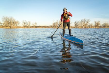senior male paddling a paddleboard on a lake in Colorado, winter or early spring scenery