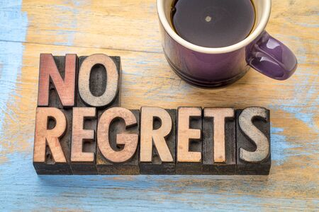 no regrets - word abstract in vintage letterpress printing blocks with a cup of coffee Stock Photo